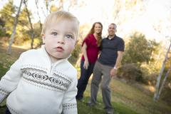 Cute Young Boy Walking in the park as Adoring Parents Look On From Behind. - stock photo