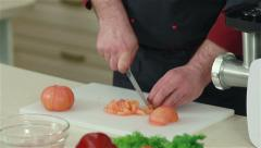 Frontal shot of chef cutting up peeled tomatoes Stock Footage