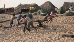Fishermen pull in their boats on the beach in Odisha province, India Stock Footage