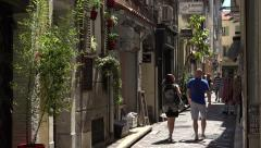 People walk down typical narrow street in old town Antibes, France Stock Footage