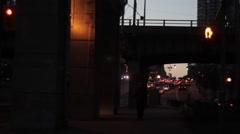 Man walks under underpass at dusk Stock Footage
