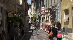 Tourists visit typical narrow street in old town Antibes, France Stock Footage