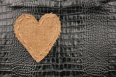 The symbolic heart from burlap lies on a crocodile  leather Stock Photos