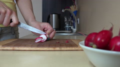 Woman hand cut radish vegetables on cutting board for salad. 4K Stock Footage