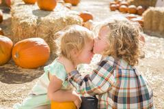 Sweet Little Boy Kisses His Baby Sister at Pumpkin Patch Stock Photos