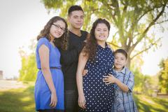 Happy Attractive Hispanic Family With Their Pregnant Mother Outdoors - stock photo