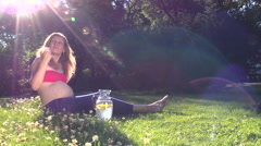 Beautiful pregnant woman drink water with lemon glass jug Stock Footage