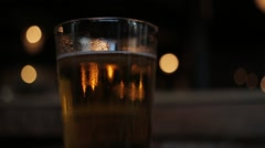 Top of Pint glass of lager on pub table middle - stock footage