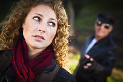 Pretty Young Teen Girl with Mysterious Strange Man Lurking Behind Her. - stock photo