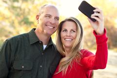 Happy, Attractive Couple Pose for a Self Portrait Outdoors. Stock Photos
