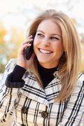 Pretty Young Blond Woman on Her Cell Phone Outside on Fall Day. Stock Photos