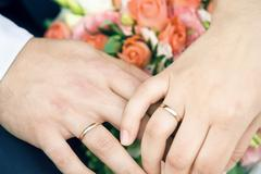Hands of happy newly-married couple with gold wedding rings and flowers Stock Photos