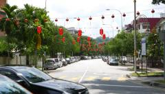 Green suburban street in sunny day, perspective, red chinese paper lanterns Stock Footage
