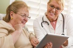 Doctor or Nurse Talking to Senior Woman with Touch Pad Computer. Stock Photos