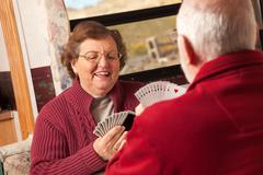 Happy Senior Adult Couple Playing Cards in Their Travel Trailer RV. - stock photo