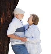 Affectionate Loving Senior Couple Leaning Against Tree Isolated on White. Stock Photos