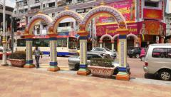 Ornate arch on sidewalk, wide empty pavement area, brickfields, tracking shot Stock Footage