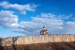 Old wood rustic church building and wooden fence against blue sky - stock photo