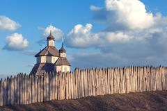 Old wood rustic church building and wooden fence against blue sky Stock Photos