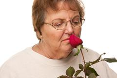 Stock Photo of Attractive Senior Woman with Red Rose Isolated on a White Background.