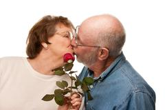 Happy Senior Husband Giving Red Rose to Wife Isolated on a White Background. Stock Photos