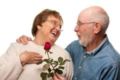 Happy Senior Husband Giving Red Rose to Wife Isolated on a White Background. - stock photo