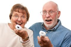 Happy Senior Couple Play Video Game with Remote Controls On a White Backgroun - stock photo