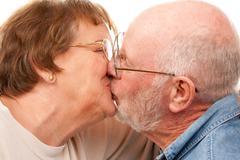 Affectionate Senior Couple Kissing Isolated on a White Background. - stock photo