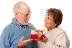 Happy Senior Couple with Gift Isolated on a White Background. - stock photo