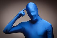 Man Wearing Full Blue Nylon Bodysuit Scratching His Head on a Grey Background Stock Photos