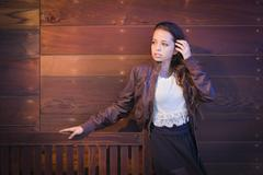 Mixed Race Young Adult Woman Portrait Against Wooden Wall - stock photo