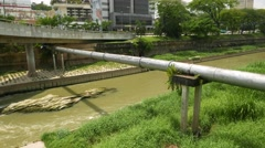 Steel pipe crossing green dreggy waters of the channel Stock Footage