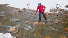 tourist enters the creek to wade with the support poles - stock footage
