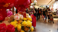Asian woman with daughter choosing artificial chrysanthemum flower Stock Footage