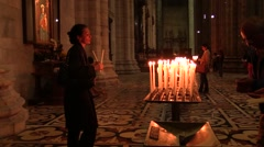 Stock Video Footage of Faithful lighting candles and praying in the Catholic Church.Milan Cathedral