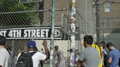 Girl checking phone, basketball on West 4th Street courts through fence, 4K NYC Stock Footage