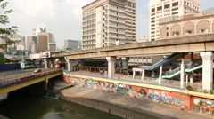 Elevated light railway transit line, canal, graffiti, bridge and Hotel Geo Stock Footage