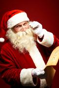 Santa reading letter - stock photo