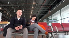 4k Couple wait for departure at the airport lounge. UHD stock footage Stock Footage
