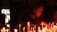 Faithful lighting candles and praying in the Catholic Church.Milan Cathedral - stock footage