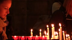 Faithful lighting candles and praying in the Catholic Church.Milan Cathedral Stock Footage