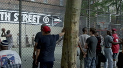 Basketball game watching through fence West 4th Street courts slow motion 4K NYC Stock Footage