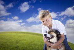Handsome Young Boy Playing with His Dog on a Lush Green Grass Field. - stock photo
