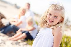Adorable Little Blonde Girl Having Fun At the Beach with Her Family. Stock Photos