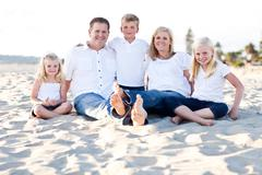 Happy Caucasian Family Portrait at the Beach One Sunny Afternoon. Stock Photos
