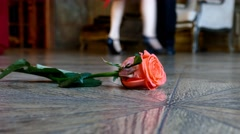 Red rose on the floor on dancing people background - stock footage