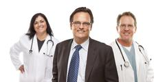 Businessman with Medical Personnel Behind Stock Photos