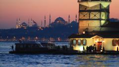 Maidens Tower and tourists during sunset in Istanbul. Tilt down from flag to sea - stock footage