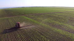 Tractor sprinkles the soybean field with chemicals in sunny spring day. Stock Footage