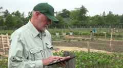 Urban Farmer looking at crops with ipad Stock Footage